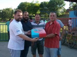 Predseda FK Dolina Miroslav Kováč (prvý zľava) od susedovcov – kovačického FK Slávia, dostal chutnú tortu