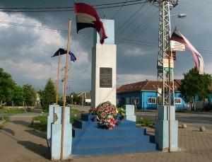 Pamätník v strede Kysáča s vlajkami a kvetmi